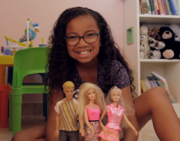 smiling girl playing with barbies