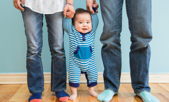toddler standing with parents holding hands