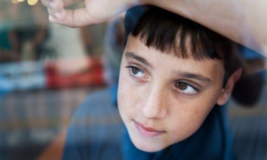 Teen boy looking out a window