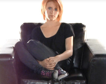 woman hugging her legs sitting on a sofa chair