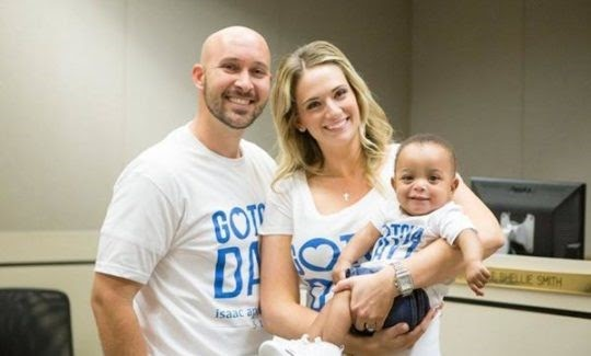 A couple holding an adopted baby - Ways to Give at Christian Family Care