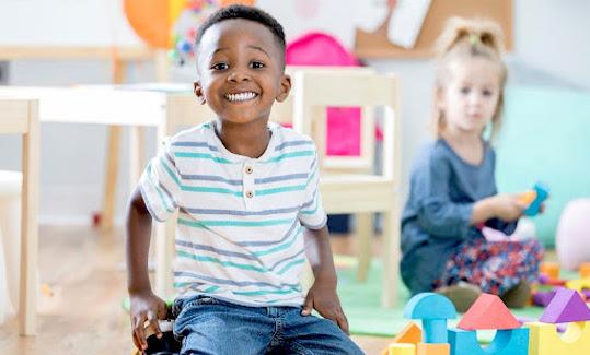 A smiling boy in a preschool classroom.